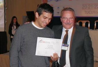 Un colega recibe en nombre de la  Dra. Isolina Iribarren del Dr. Ricardo Videla el diploma correspondiente
